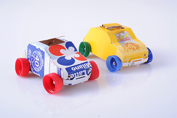 Recycled juice cartons and plastic bottle caps make great toy cars!